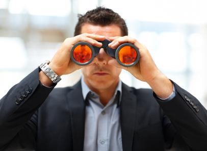 Entrepreneur with binoculars looking to future